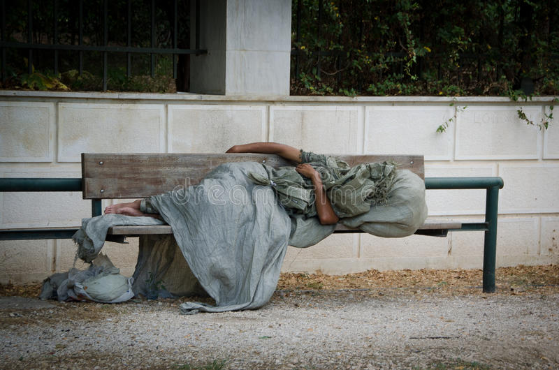 Homeless man. Athens,Greece, - November 4, 2015: Homeless man is sleeping on a bench in the center of Athens.After six years of hard austerity imposed by the royalty free stock image