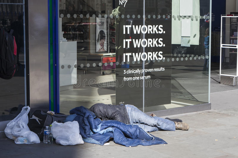 Homeless man begging on Oxford street, London. LONDON, ENGLAND - August 25 , 2016 Homeless man wrapped in blanket lying on Oxford street, London stock image