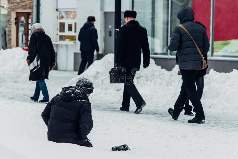 Homeless man begs for alms knees in the snow. Homeless man begging sitting in the snow in Russia royalty free stock photography