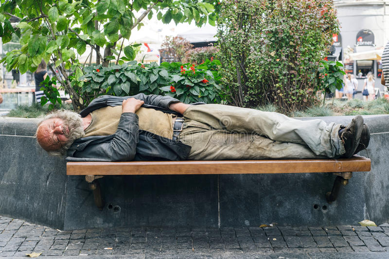 Homeless man. BELGRADE,SERBIA - AUGUST 10, 2015: Unidentified Serbian homeless man with hand in the pants sleeps on a bench in Serbia, Aug 10, 2015 royalty free stock photo