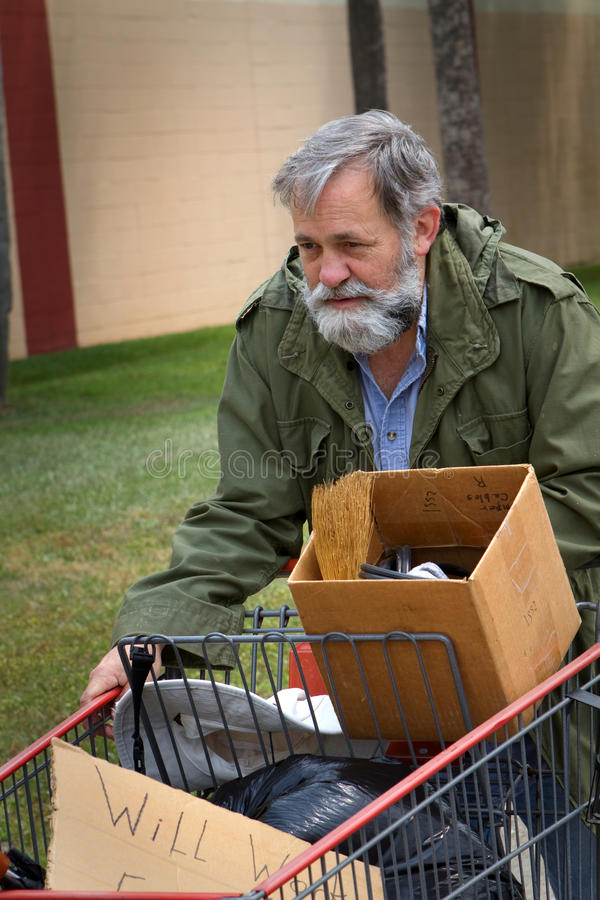 Homeless Man Cart. Homeless man wearing an old army coat pushes a shopping cart holding his possessions royalty free stock photography