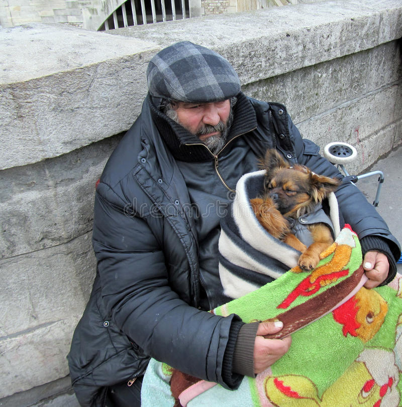 Homeless man with Dogs in Notre Dame, Paris. royalty free stock photography