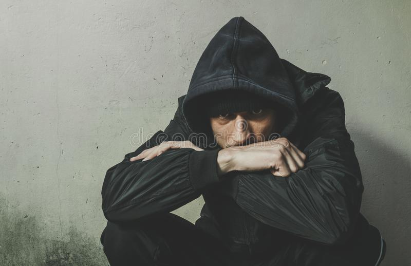 Homeless man drug and alcohol addict sitting alone and depressed on the street in winter clothes feeling anxious cold and lonely, stock image
