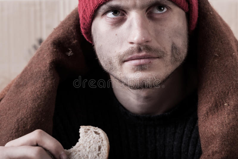Homeless man eating a piece of bread royalty free stock photography