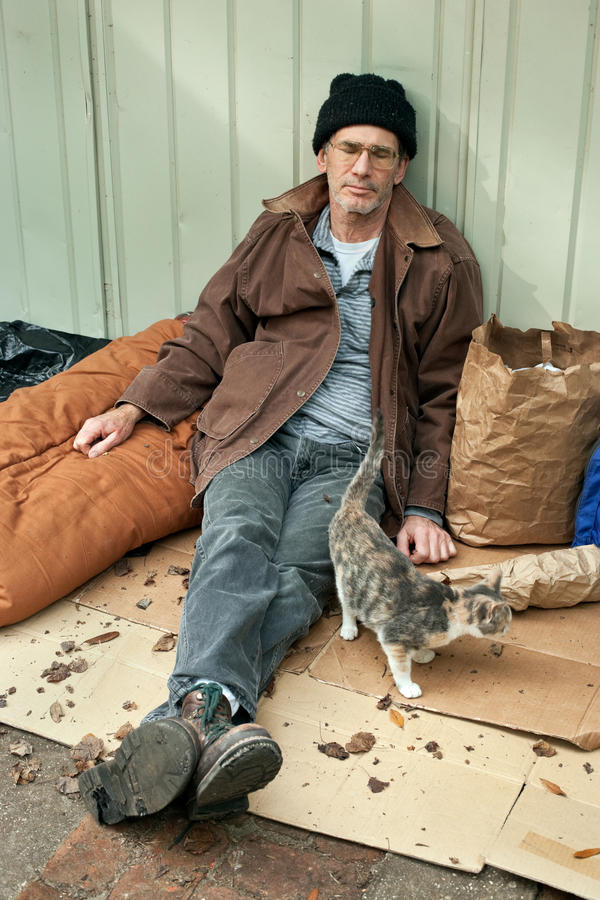 Homeless Man and Friendly Stray Cat. Resigned looking mature homeless man seated on the street with watching a friendly stray cat stock photos
