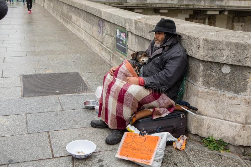 A homeless man with his dog in Paris stock photo