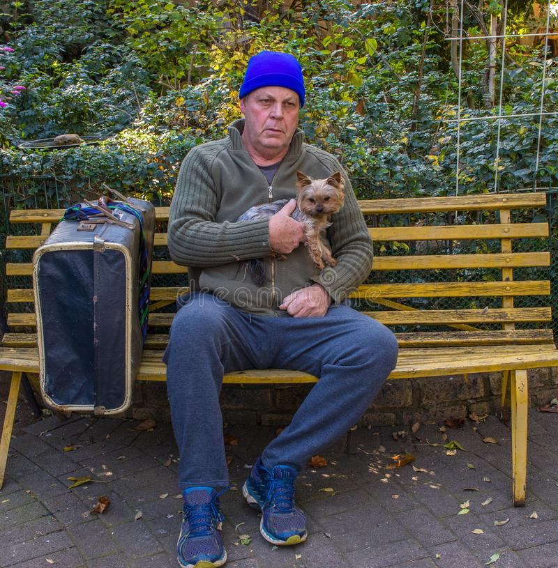 Homeless man and his dog sit on a park bench. Homeless caucasian man sit on a yellow park bench with his dog and his belongings image with copy space in stock image