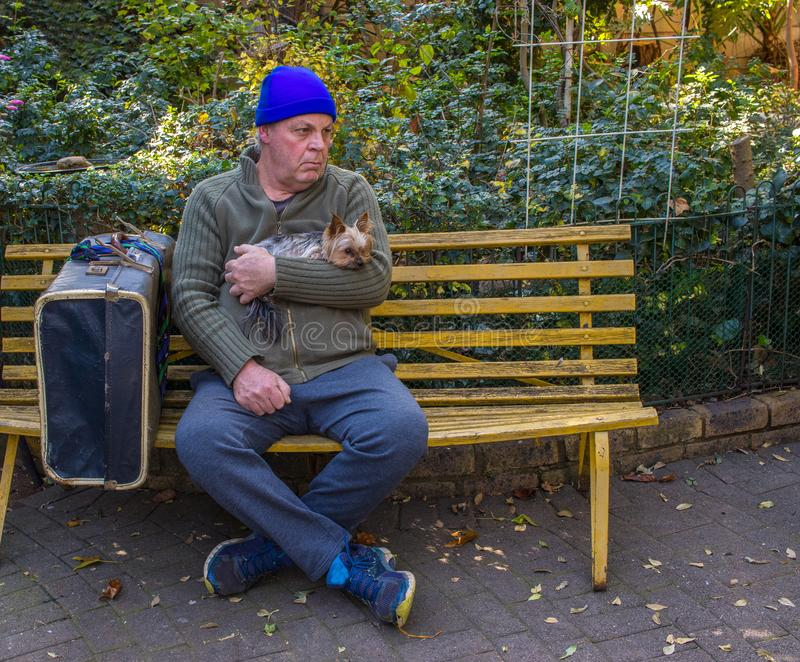 Homeless man and his dog sit on a park bench stock photo