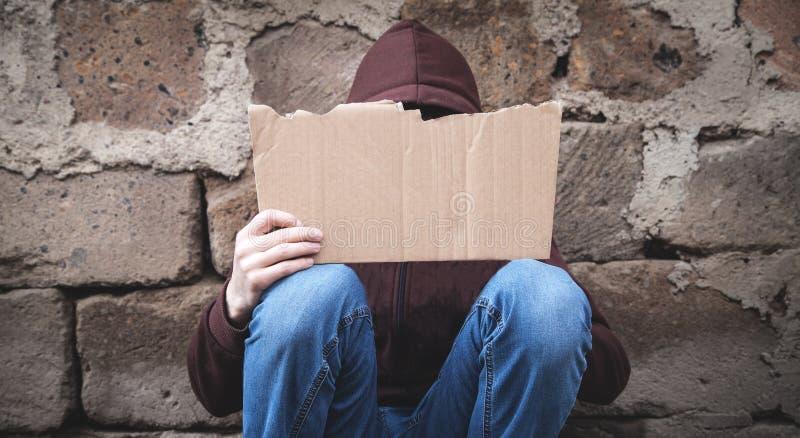 Homeless man holding blank cardboard stock images