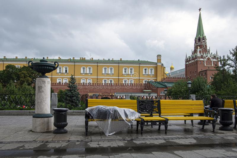 Homeless man lies on a bench in the center of the Russian capital. Moscow, red square, under plastic wrap sleeping poor man affec. A homeless man lies on a bench stock photos