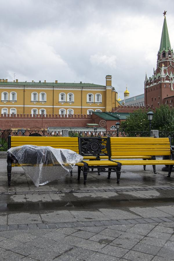 Homeless man lies on a bench in the center of the Russian capital. Moscow, red square, under plastic wrap sleeping poor man affect. A homeless man lies on a stock photo