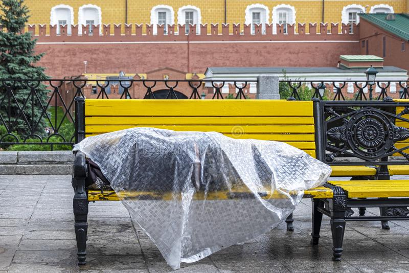 Homeless man lies on a bench in the center of the Russian capital. Moscow, red square, under plastic wrap sleeping poor man affect. A homeless man lies on a royalty free stock image