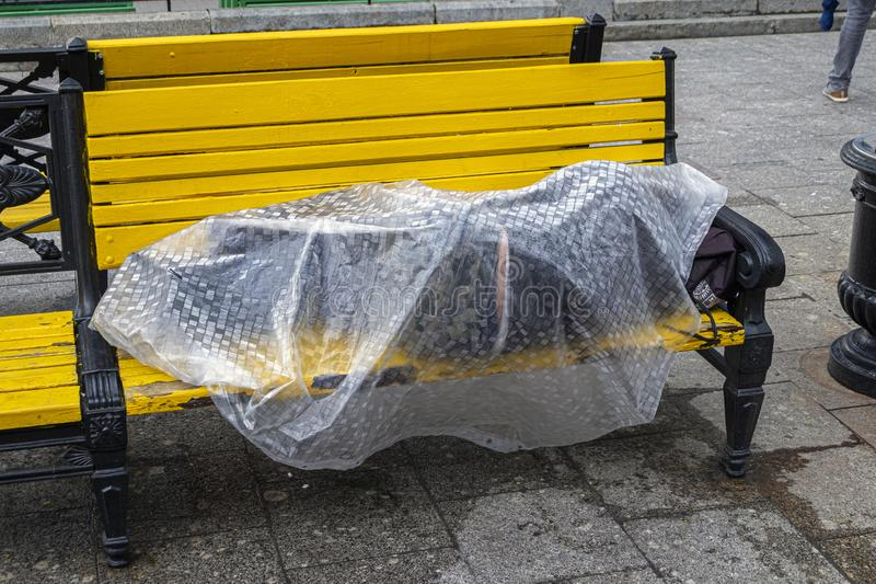 Homeless man lies on a bench in the center of the Russian capital. Moscow, red square, under plastic wrap sleeping poor man affect. A homeless man lies on a royalty free stock images