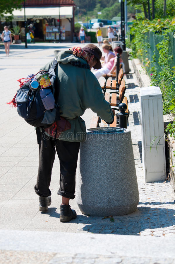 Homeless man looking for food in the trash. Poor homeless man looking for food in the trash royalty free stock images