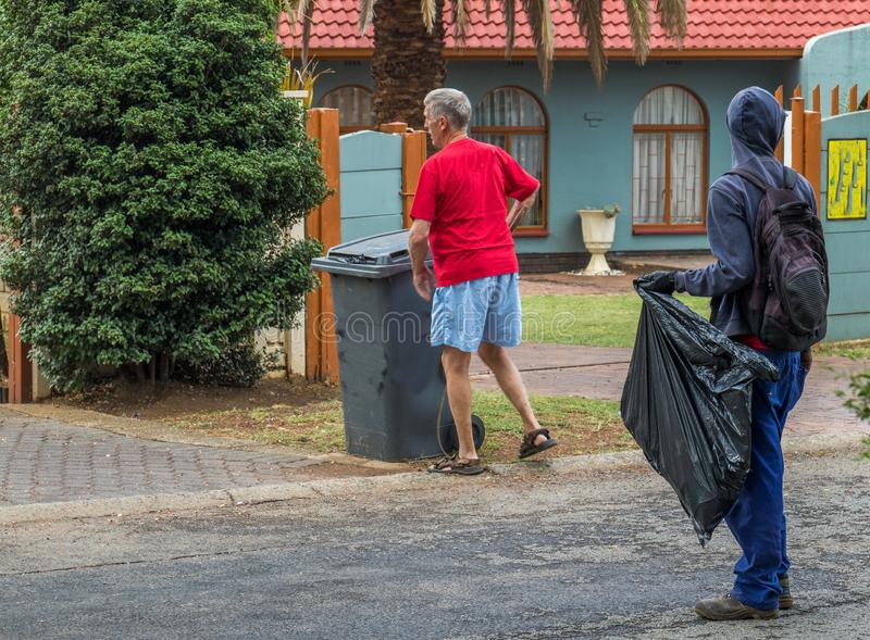 Homeless man picks refuse bins in South Africa. Johannesburg, South Africa - unidentified homeless man waits for an unidentified homeowner to place a refuse bin royalty free stock photo