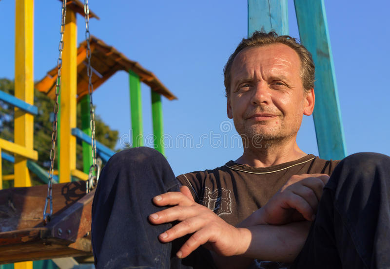 Homeless Man. Poor people in the children`s Playground at sunse. Homeless Man. Bum. Poor people in the children`s Playground at sunset in the summer royalty free stock photography