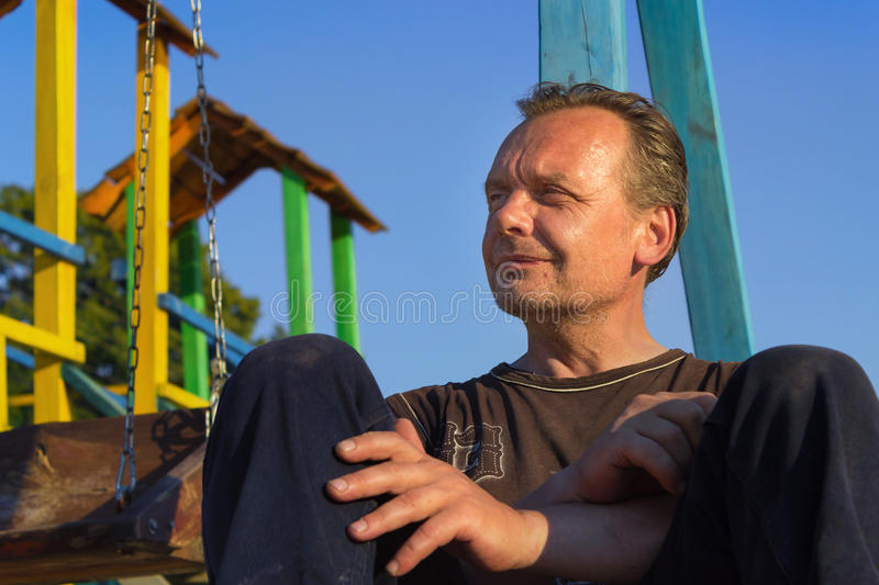 Homeless Man. Poor people in the children`s Playground at sunse. Homeless Man. Bum. Poor people in the children`s Playground at sunset in the summer royalty free stock image