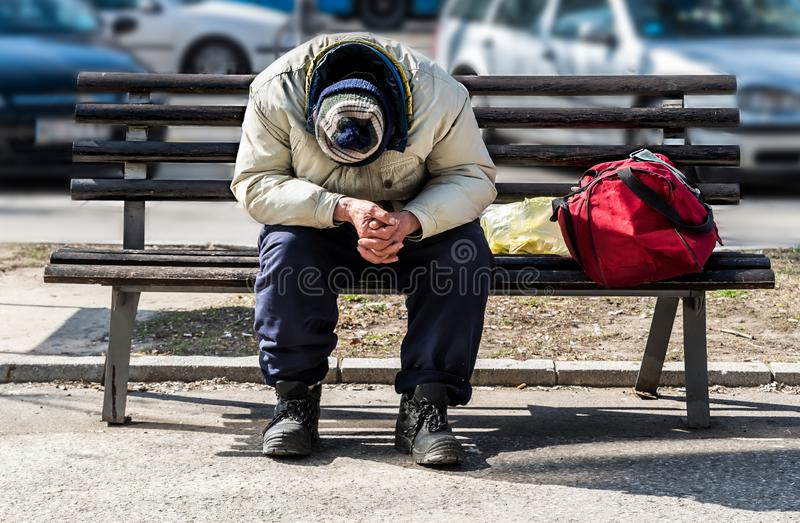 Homeless man, Poor homeless man or refugee sleeping on the wooden bench on the urban street in the city with bags of clothes and j. Unk on sunny cold day, social royalty free stock photography