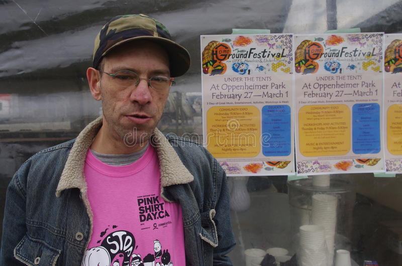 Man by a poster of festival for homeless stock photos