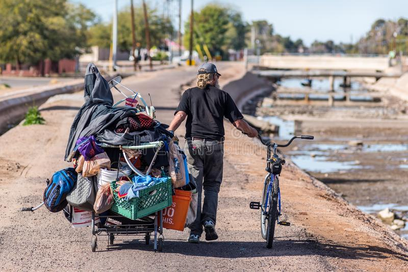 Homeless Man Pulling Cart. A homeless man in Phoenix pulls an overladen shopping cart along a path next to the Arizona Canal. At the time of the photo the canal stock photography