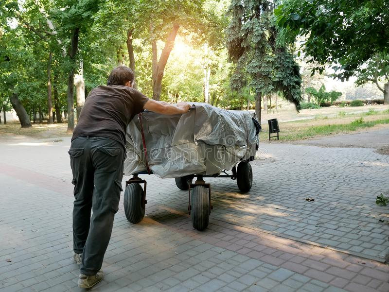 A homeless man pushes a cart in front of him stock images