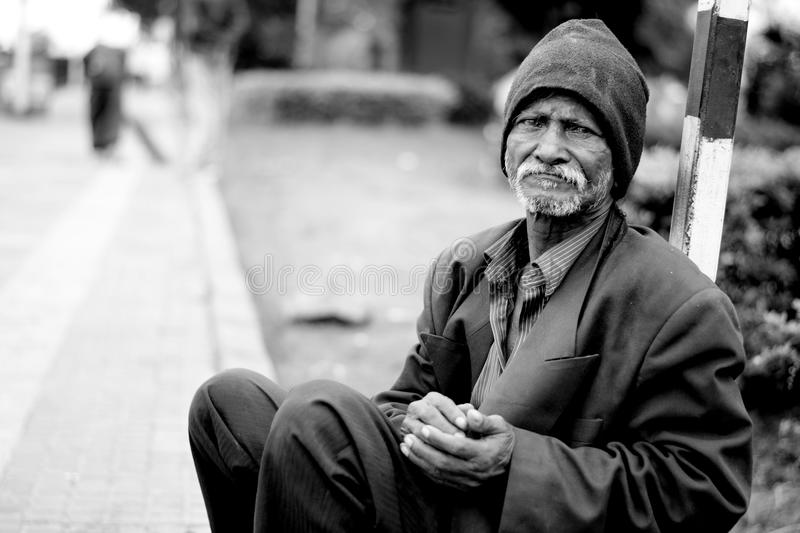 Homeless man sat in street stock photography