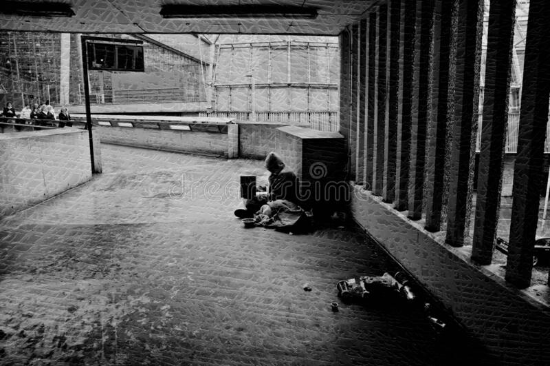 Homeless man sitting in a passageway stock photos
