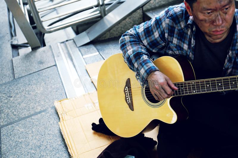 Asia homeless man sitting and playing acoustic guitar on walking street in the capital city. stock photo