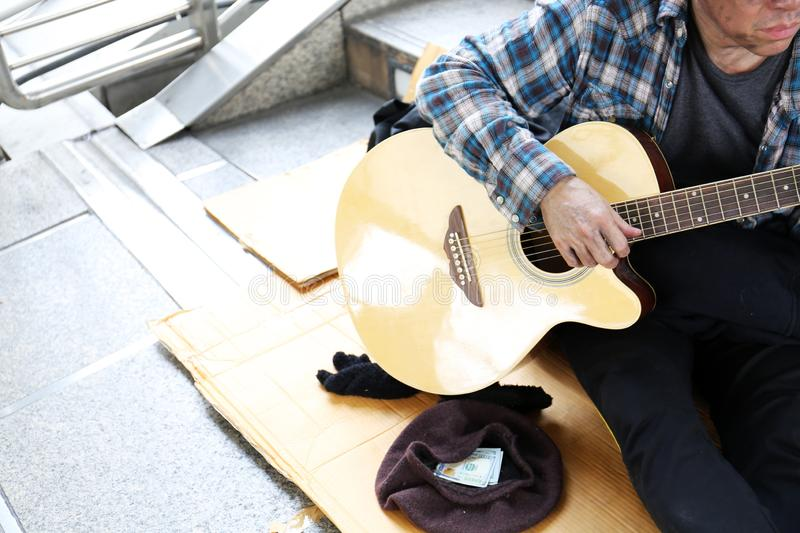 Homeless man sitting and playing acoustic guitar on walking street in the capital city. Asia Homeless man sitting and playing acoustic guitar on walking street royalty free stock image