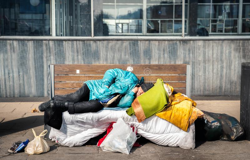 Poor homeless man or refugee sleeping on the wooden bench on the urban street in the city with bags of clothes and junk on sunny c royalty free stock photos