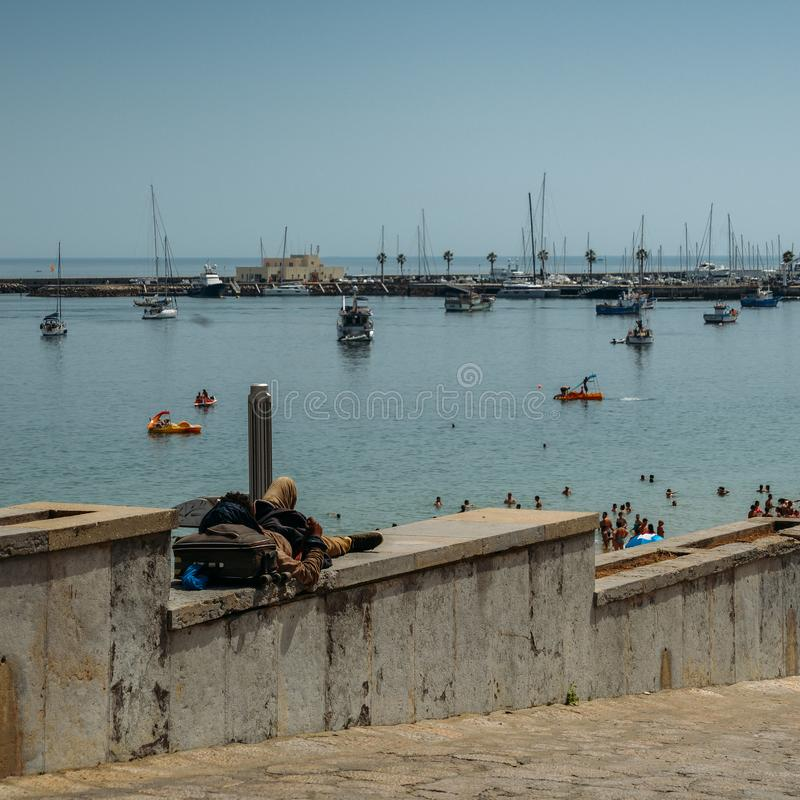 Homeless man sleeping rough overlooking the beautiful bay and luxury yachts in Cascais. Cascais, Portugal - August 3rd, 2018: Homeless man sleeping rough royalty free stock images
