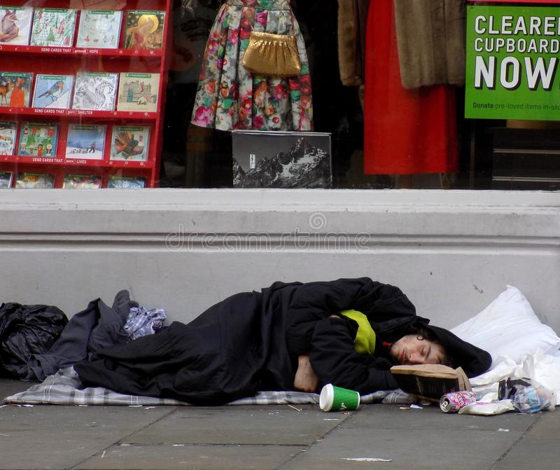 Homeless man sleeping rough on street. A homeless rough-sleeper in the city centre of Liverpool. This young man was lying in front of a charity shop, but mostly royalty free stock image
