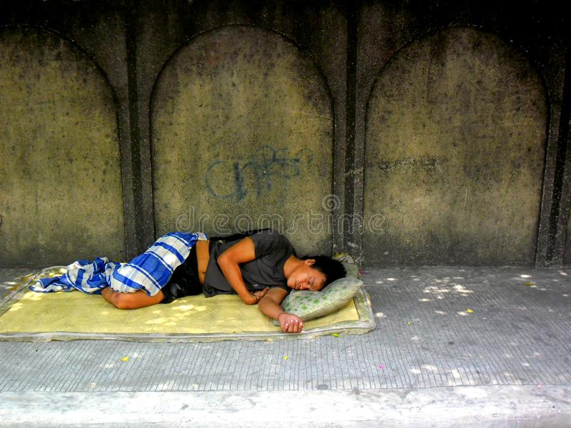 Homeless man sleeping on a sidewalk. Photo of a Homeless man sleeping on a sidewalk in the streets of cubao, quezon city in philippines, asia stock images