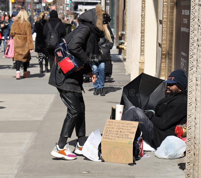 Homeless man at 5th Avenue in Midtown Manhattan. NEW YORK - MARCH 7, 2019: Homeless man at 5th Avenue in Midtown Manhattan stock photography