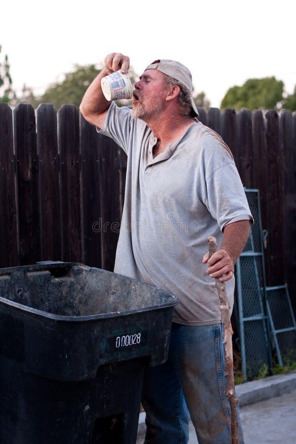 Homeless man trash picking royalty free stock photography