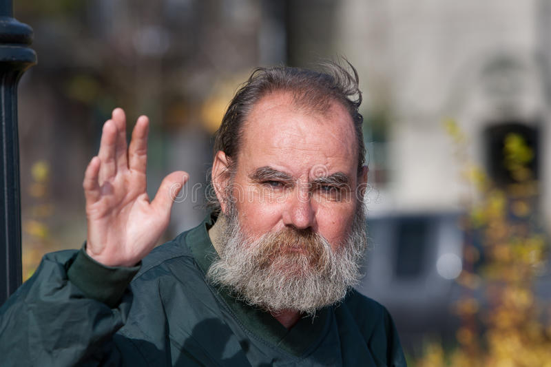 Homeless man waving. While outdoors during the daytime royalty free stock photos