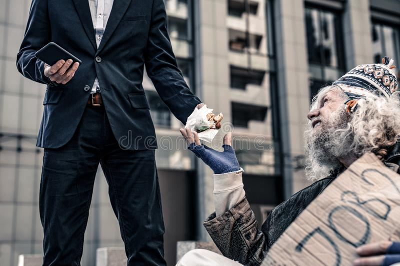 Desperate starving old man sitting on cold ground and begging for food royalty free stock images