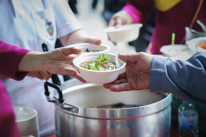Homeless and needy people receive help, receive food from volunteers : concept of food donation.  royalty free stock photos