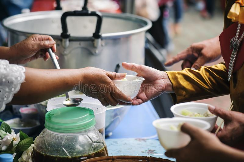 Homeless and needy people receive help, receive food from volunteers : concept of food donation.  stock photo
