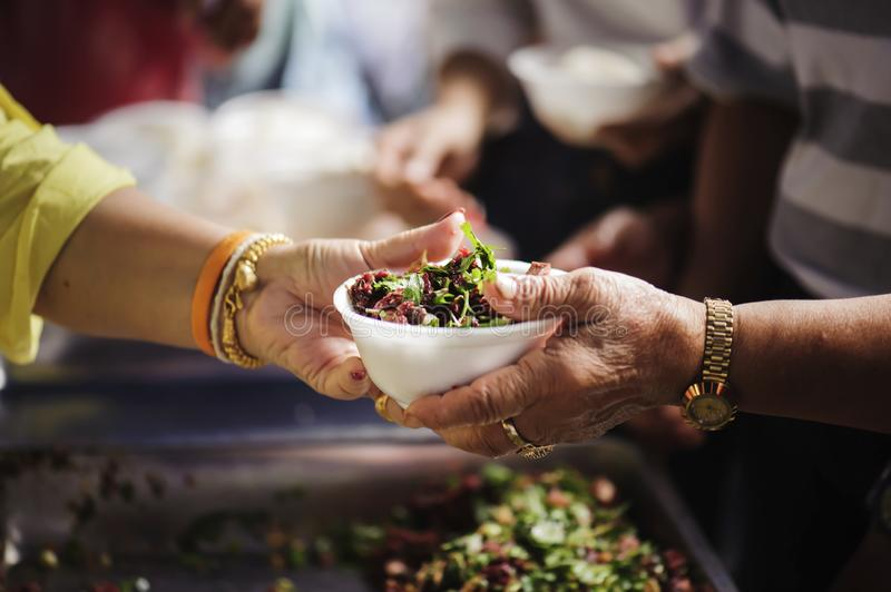 Homeless and needy people receive help, receive food from volunteers : concept of food donation.  royalty free stock images