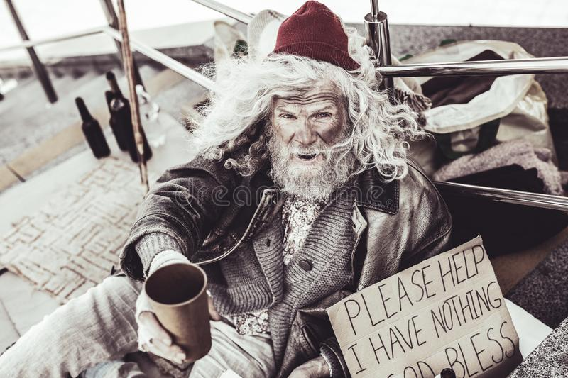 Homeless old man trying to move to pity pedestrians. royalty free stock images