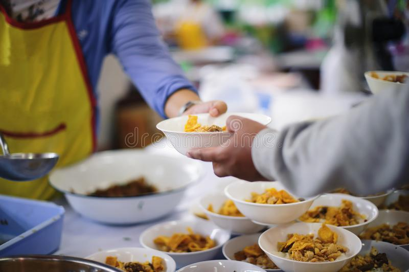 Homeless people pick up charity food from the food donors in society : concept homelessness.  stock photo