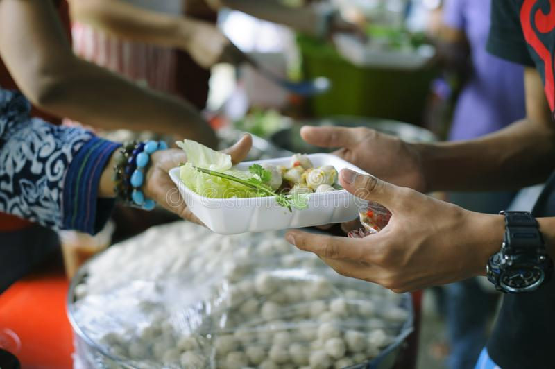 Homeless people pick up charity food from the food donors in society : The concept of the beggar problem on earth : The Hand of. The Beggars receives charity royalty free stock image