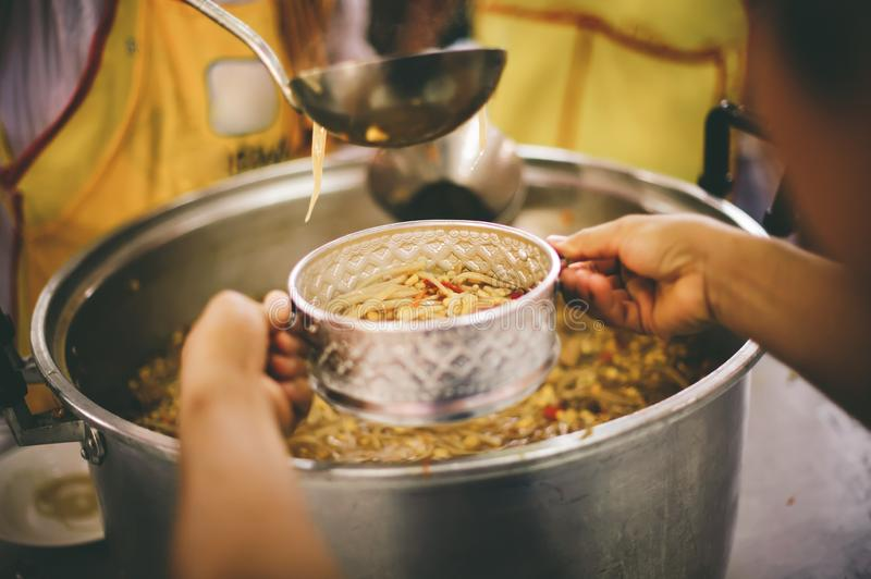 Homeless people receive delicious charity food from volunteers: concept of helping by donating food.  royalty free stock photos