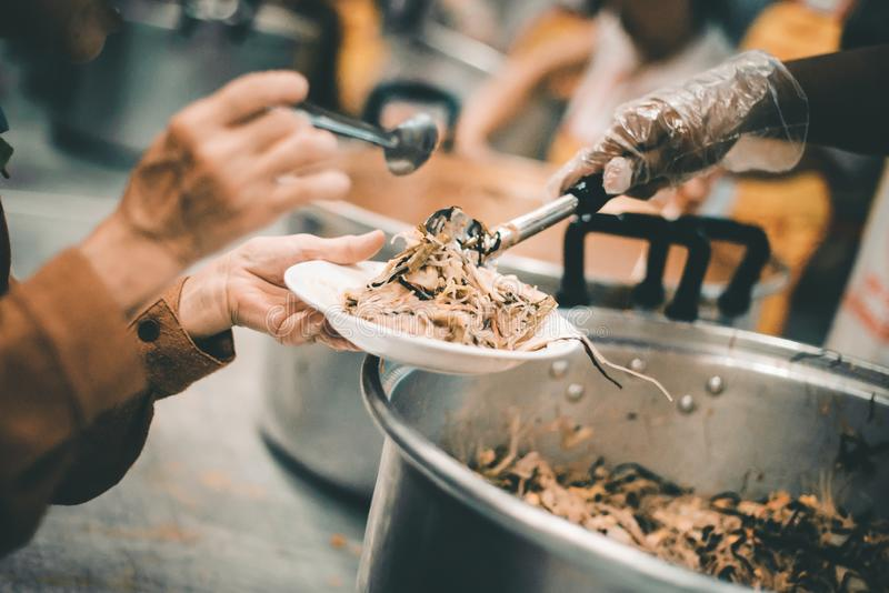 Homeless people receive delicious charity food from volunteers: concept of helping by donating food.  stock image