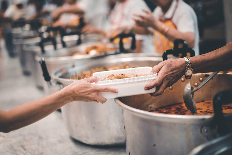 Homeless people receive delicious charity food from volunteers: concept of helping by donating food.  royalty free stock photo