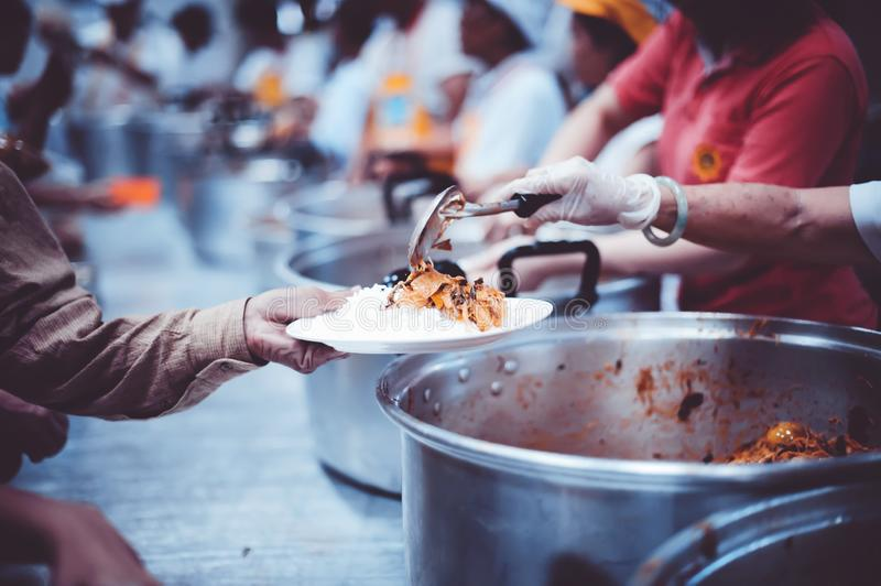Homeless people receive free charity food from the hands of volunteers : concept of hunger problems in a helping society.  royalty free stock photography