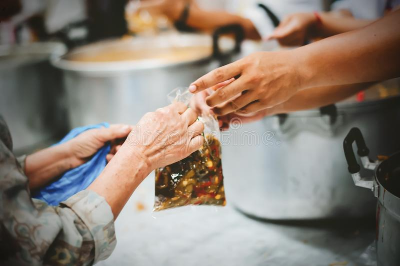 Homeless people receive free charity food from the hands of volunteers : concept of hunger problems in a helping society.  stock images
