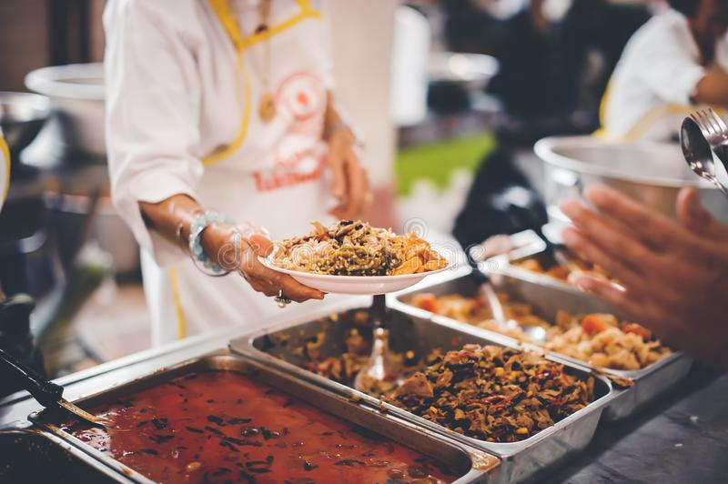 Homeless people receive free charity food from the hands of volunteers : concept of hunger problems in a helping society.  stock photo