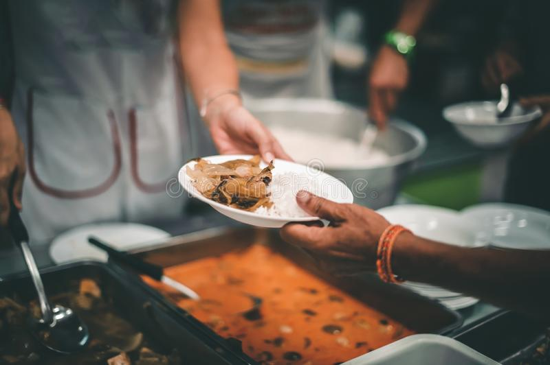 Homeless people receive free charity food from the hands of volunteers : concept of hunger problems in a helping society.  stock photos